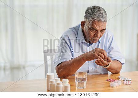 Portrait of senior Indian man taking various pills