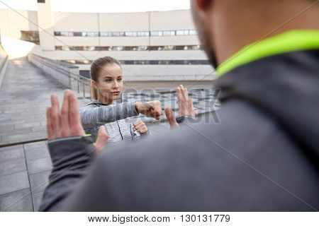 fitness, sport, people, exercising and martial arts concept - young woman with trainer working out self defense strike on city street