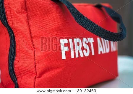 A red first aid kit bag with a black zip and handle in closeup.