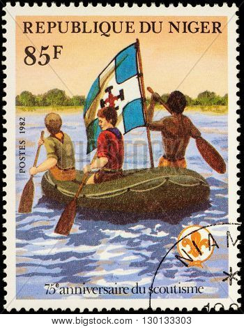MOSCOW RUSSIA - MAY 14 2016: A stamp printed in Niger shows three scout floating in an inflatable boat on the river series