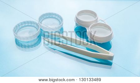 Contact lenses set with contact lenses tweezers contact lenses plastic case with solution on blue background