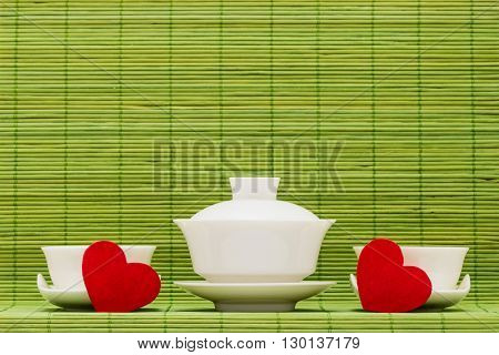 Gaiwan drinking bowls for the Chinese tea and heart against green bamboo sticks