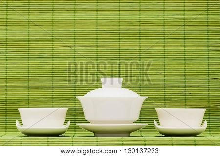 Gaiwan and drinking bowls for the Chinese tea against green bamboo sticks