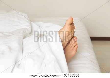 Under the covers with feet showing in a bed