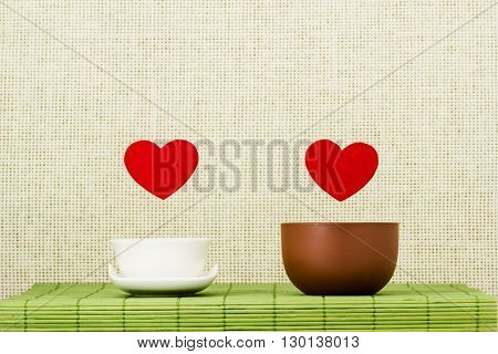 Two symbols of heart and love hang on threads over drinking bowls for tea