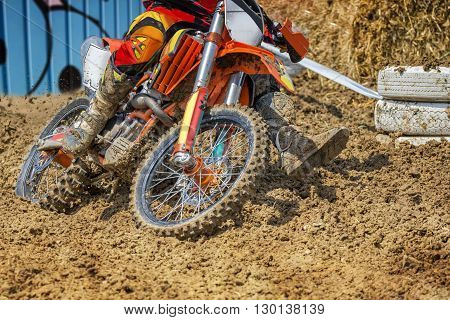 Action packed scene of a moto cross rider in a race who plows through deep mud.