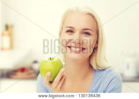 healthy eating, organic food, fruits, diet and people concept - happy woman eating green apple over kitchen background