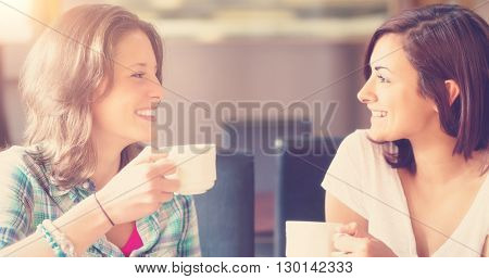 Two smiling students having a cup of coffee in college canteen
