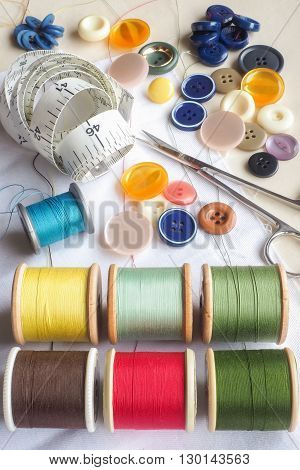 A collection of haberdashery items including - an assortment of colored cottons buttons scissors a dressmaker's measuring tape and a piece of white cloth.