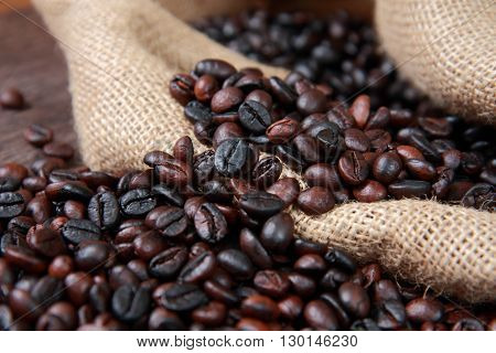 Dark roasted coffee beans in gunny sack close up image