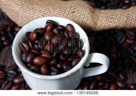 Dark roasted coffee beans in white cup with blurred coffee beans and gunny sack texture on background
