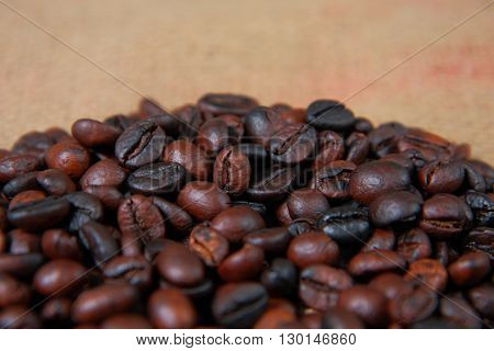 Dark roasted coffee beans on gunny sack texture