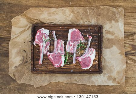 Raw lamb chops. Rack of Lamb with rosemary and spices on rustic chopping board over oily craft paper and old wooden background, top view