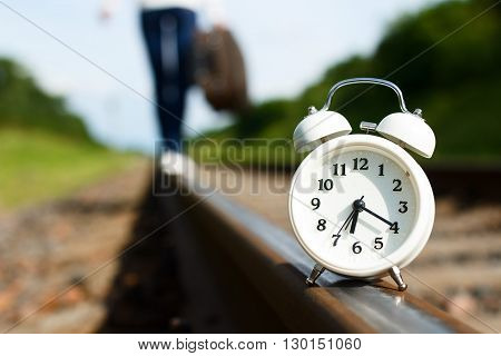 In sunny summer day white alarm clock is standing on rails at the foreground and girl with suitcase is going away on rails blurred at the background