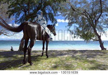 Muslim woman wearing hijab riding horse on puru kambera beach sumba indonesia