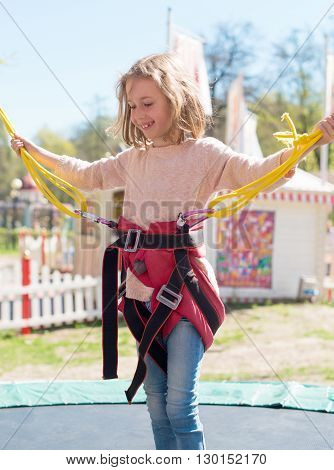 Little Girl On Bungee Trampoline With Cords.