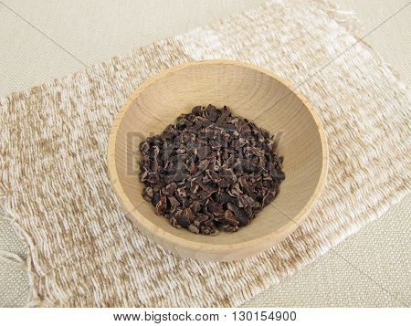 Cocoa nibs in small wooden bowl on table