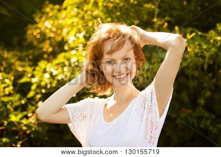 Portrait of joyful girl dressed in white blouse at nature background in sunny summer day