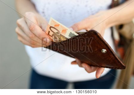 Girl is taking out a banknote of fifty euros from brown leather wallet on the street. Hands money and wallet close-up