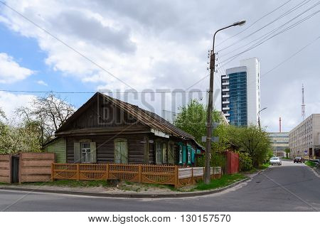GOMEL BELARUS - APRIL 20 2016: Spot construction in city center. Extant private sector and modern building of BelNIPIneft (Belorussian Scientific-Research and Design Institute of Petroleum) on Knizhnaya and Telman streets