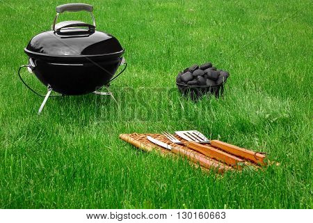 Portable Barbecue Grill Appliance And Tools On The Fresh Lawn