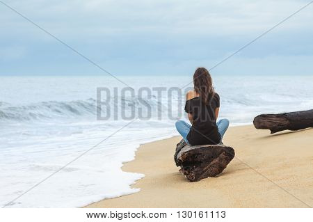 Lonely woman sitting on the tropical beach by the sea.