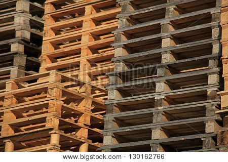 Stacked wooden shipping pallets at a storage