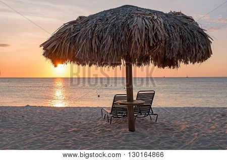 Grass umbrellas at the beach on Aruba island at sunset