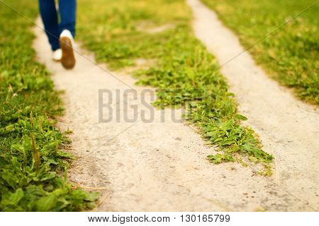 Fork of sandy footpath in green grass and feet of going person. Summer sunny day. Blurred background