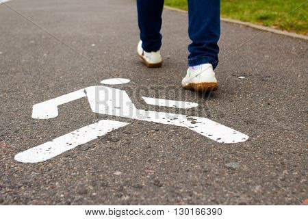 White sign of pedestrian zone on asphalted sidewalk and feet of pedestrian in summertime