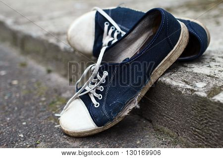 Shabby textile holey blue gumshoes with white laces had abandoned at the street in summer
