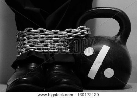 Businessman legs dressed in black trousers and shoes is fastening by metal chain to black iron kettlebell with drawn percent sign. Concept of percent payments. Monochrome image