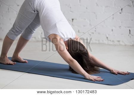 Attractive Young Woman Doing Downward Facing Dog Pose In White Loft