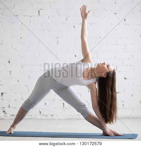 Side View Portrait Of Happy Woman Doing Extended Triangle Pose