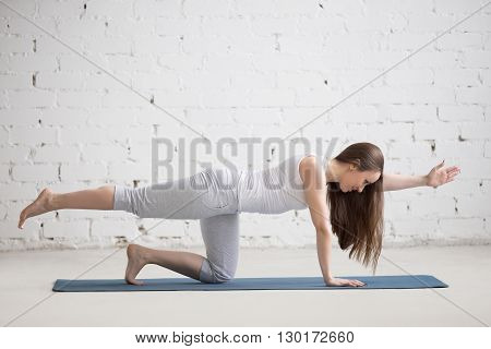 Portrait Of Beautiful Woman Doing Bird-dog Pose