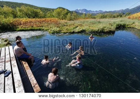 NALYCHEVO NATURE PARK, KAMCHATKA PENINSULA, RUSSIA - SEP 7, 2013: Group hot springs in Nalychevo Nature Park - people take a therapeutic (medicinal) baths in pool with natural thermal mineral water having balneological properties.