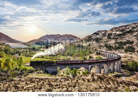 Glenfinnan Railway Viaduct In Scotland With The Jacobite Steam Train Against Sunset Over Lake