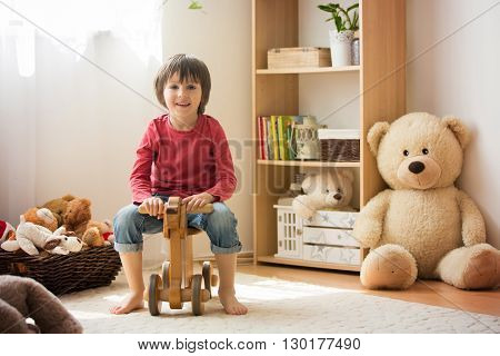 Sweet Little Boy, Preschool Child, Playing At Home With Wooden Horse