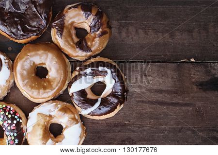 Background of chocolate carmel glazed and filled donuts over a rustic background with copy space. Image shot from overhead.