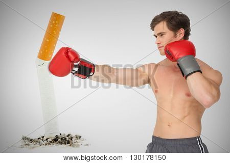 Muscly man wearing red boxing gloves and punching against image of pressed cigarette on a white background