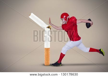 American football player jumping with the ball against beige background