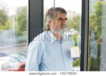Old Men With A Cup Of Coffee Next To A Window
