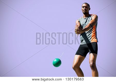 Sporty man playing at hammer throw against purple background