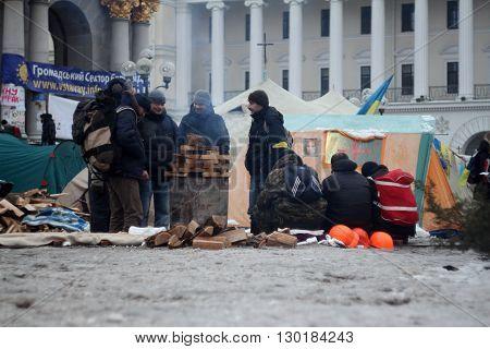 Kiev, Ukraine - December 11, 2013: Mass anti-government protests EuroMaydan in the center of Kiev (Maidan Nezalezhnosti). Protesters are heated by the fire on December 11, 2013 in Kiev, Ukraine