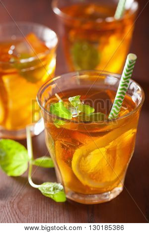 ice tea with lemon and mint on dark rustic background