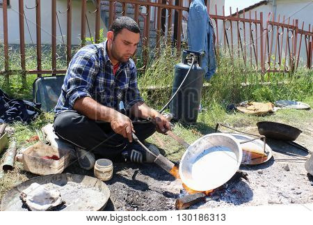 RESEN MACEDONIA. MAY 18 2016: Young traveling artisan retinning old copper dish in village of Carev DvorResen Macedonia
