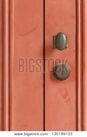 Close up retro doorknob on red door.