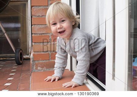 portrait of blonde caucasian baby nineteen month age chubby face looking at camera peering terrace floor supported on the arms