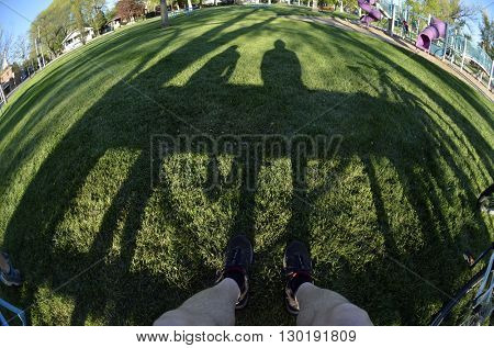 Person sitting on park bench shadows relaxing fisheye