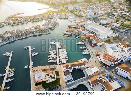 Aerial view of the beautiful Marina in Limassol city in Cyprus the beach boats piers villas and commercial area. A very modern high end and newly developed space where yachts are moored and it's perfect for a waterfront promenade. poster